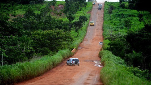 carros sofrendo com uma estrada esburacada
